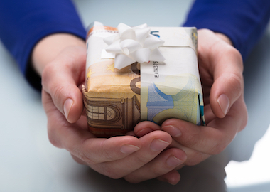 Woman's Hand Holding Gift Wrapped With Banknotes